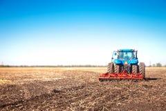 在领域的蓝色拖拉机 免版税库存图片