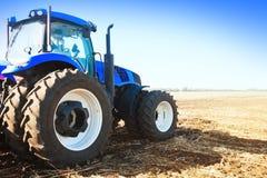 在领域的蓝色拖拉机 库存照片