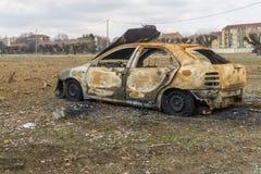在领域的被烧的汽车击毁和作为背景的城内住宅 免版税库存照片