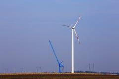 在领域的风轮机在起重机旁边 免版税库存图片