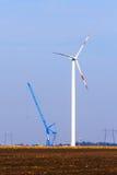 在领域的风轮机在起重机旁边 库存图片