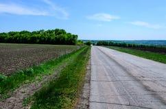 在领域附近的柏油路 免版税库存图片
