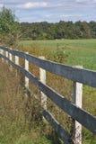 在领域附近的白色篱芭 免版税图库摄影