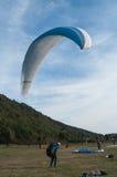 在领域登陆的滑翔伞 免版税库存图片