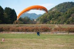 在领域登陆的滑翔伞 图库摄影