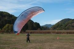 在领域登陆的滑翔伞 免版税图库摄影