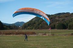在领域登陆的滑翔伞 库存照片