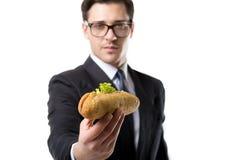 在领带和衣服的年轻商人吃热狗 库存照片