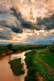 在颜色云彩之下的河 免版税库存照片