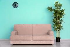 在颜色墙壁附近的时髦的沙发 免版税库存图片