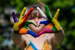 在颜色油漆的孩子手做心脏形状,在手上的焦点 免版税库存照片
