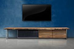 在颜色混凝土墙上的电视有木桌内部葡萄酒猪圈的 库存图片