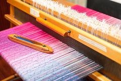 在颜色的编织的梭在织机翘曲 免版税库存照片