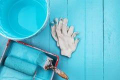 在颜色盘子的画笔和油漆用桶提,在蓝色木的手套 库存照片