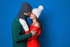在颜色背景的年轻夫妇 庆祝庆祝圣诞节女儿帽子母亲圣诞老人佩带 免版税库存照片