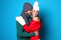 在颜色背景的年轻夫妇 庆祝庆祝圣诞节女儿帽子母亲圣诞老人佩带 免版税图库摄影