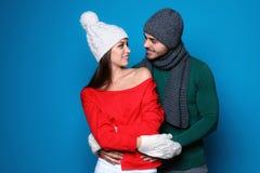 在颜色背景的年轻夫妇 庆祝庆祝圣诞节女儿帽子母亲圣诞老人佩带 库存照片