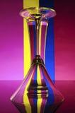 在颜色背景(桃红色、蓝色,黄色)的玻璃 免版税库存图片