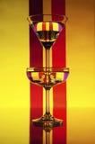 在颜色背景(红色,桃红色,黄色)的玻璃 免版税库存照片