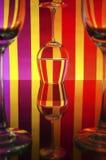 在颜色背景(红色,桃红色,黄色)的玻璃 库存图片
