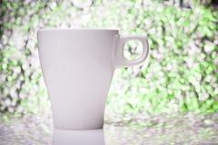 在颜色defocused背景的白色茶杯 免版税库存照片