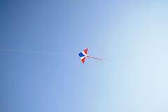 在风和清楚的天空的风筝飞行 免版税库存图片