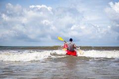 在风大浪急的海面供以人员用浆划在大波浪的皮船 免版税库存照片