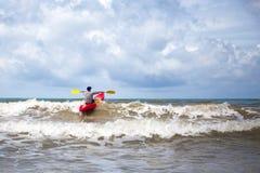 在风大浪急的海面供以人员用浆划在大波浪的皮船 免版税库存图片