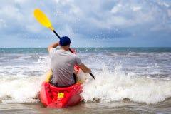 在风大浪急的海面供以人员用浆划在大波浪的皮船 库存照片