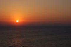 在风平浪静上的橙色日落 免版税库存图片