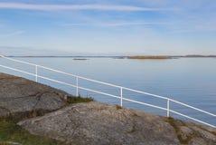 在风平浪静前面的白色栏杆 免版税库存照片