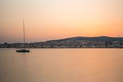 在风平浪静和城市的美好的日落 免版税库存照片