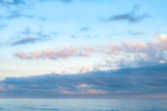 在风平浪静水上的美丽如画的cloudscape 免版税库存图片