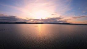 在风平浪静水的鸟瞰图在与山的五颜六色的日落期间在背景 影视素材
