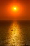 在风平浪静的红色日落 免版税库存图片
