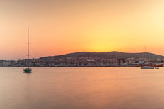 在风平浪静的美好的日落有小船和城市的 图库摄影