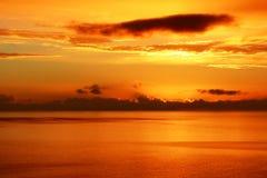 在风平浪静的黄光日落的 免版税库存图片