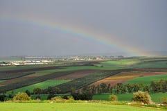 在风景、村庄和领域的彩虹 免版税库存图片