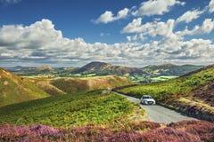 在风景小山上面的白色汽车有惊人的看法 库存图片