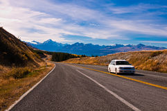 在风景山路的迷离白色汽车 免版税库存图片