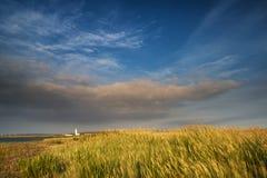 在风景的灯塔在Summ的剧烈的风雨如磐的天空日落下 免版税库存照片
