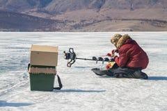 在风景贝加尔湖的冬天冰渔期间一个年轻人插入钓丝入钓鱼竿 免版税图库摄影
