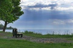 在风暴以后的天空在与树、长凳和湖的夏天作为风景 免版税库存照片