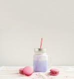 在风格化金属螺盖玻璃瓶杯子的紫色咖啡有macarons和五颜六色的装饰的 蓝莓奶昔, cocktaill, frappuccino Unico 库存图片
