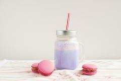 在风格化金属螺盖玻璃瓶杯子的紫色咖啡有macarons和五颜六色的装饰的 蓝莓奶昔, cocktaill, frappuccino Unico 免版税库存照片