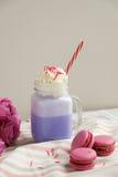 在风格化金属螺盖玻璃瓶杯子的紫色咖啡有macarons和五颜六色的装饰的 蓝莓奶昔 独角兽咖啡 库存照片