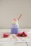 在风格化金属螺盖玻璃瓶杯子的紫色咖啡有macarons和五颜六色的装饰的 蓝莓奶昔 独角兽咖啡 库存图片