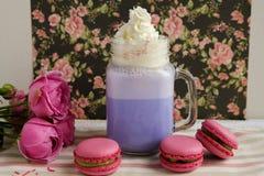 在风格化金属螺盖玻璃瓶杯子的紫色咖啡有macarons和玫瑰的和在花卉样式背景的五颜六色的装饰  蓝莓 库存图片