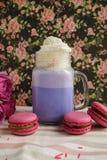 在风格化金属螺盖玻璃瓶杯子的紫色咖啡有macarons和玫瑰的和在花卉样式背景的五颜六色的装饰  蓝莓 库存照片