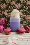 在风格化金属螺盖玻璃瓶杯子的紫色咖啡有macarons和玫瑰的和在花卉样式背景的五颜六色的装饰  蓝莓 图库摄影